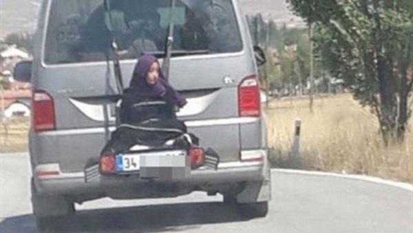 رجل يربط أبنته في حقيبة السيارة